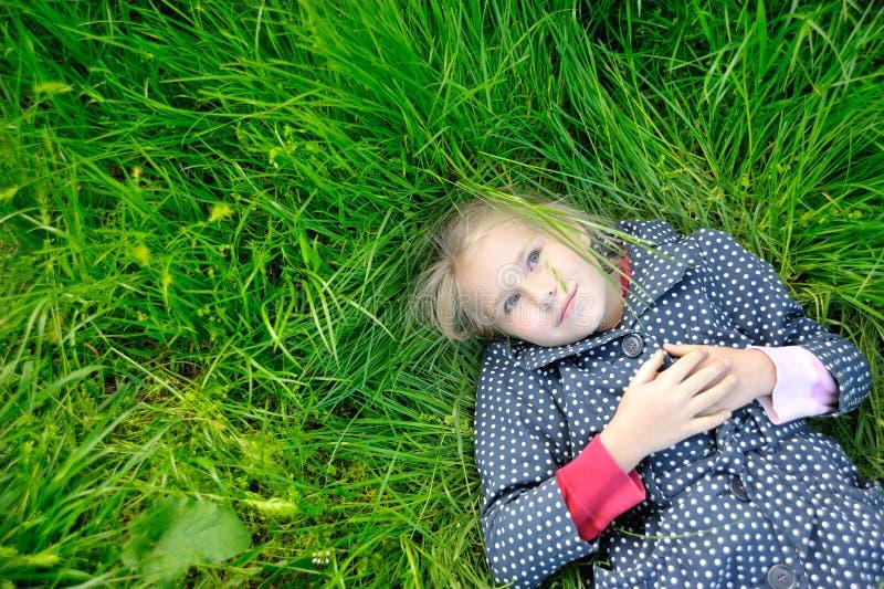 Niña feliz que sueña en la hierba y que disfruta de verano imagen de archivo libre de regalías