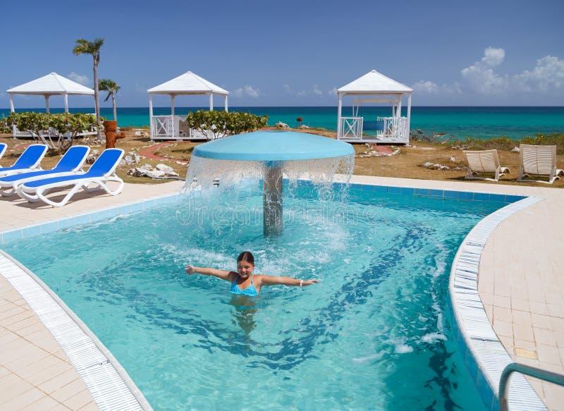 Niña feliz sonriente que goza de nadar y de la relajación en piscina de agua con la agua de mar natural fotografía de archivo