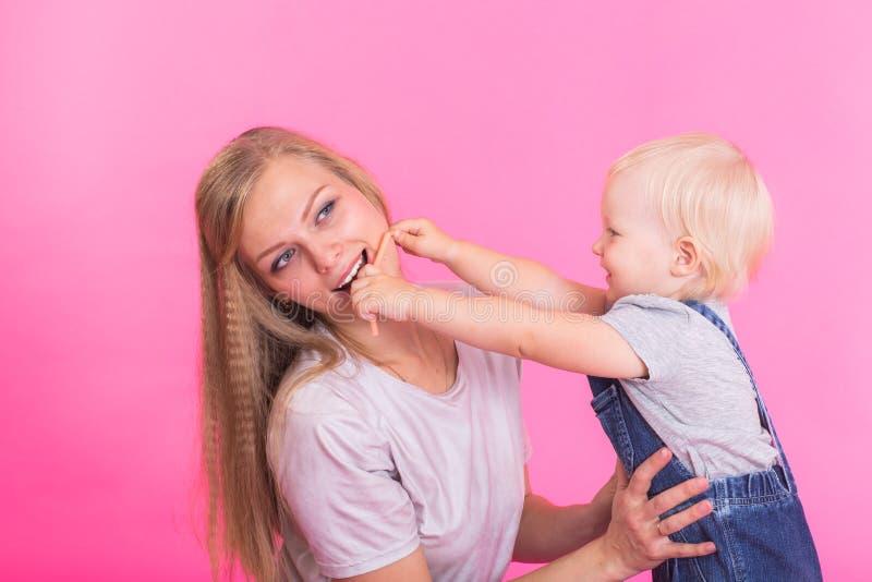 Niña feliz y su madre que se divierten sobre fondo rosado imagen de archivo libre de regalías