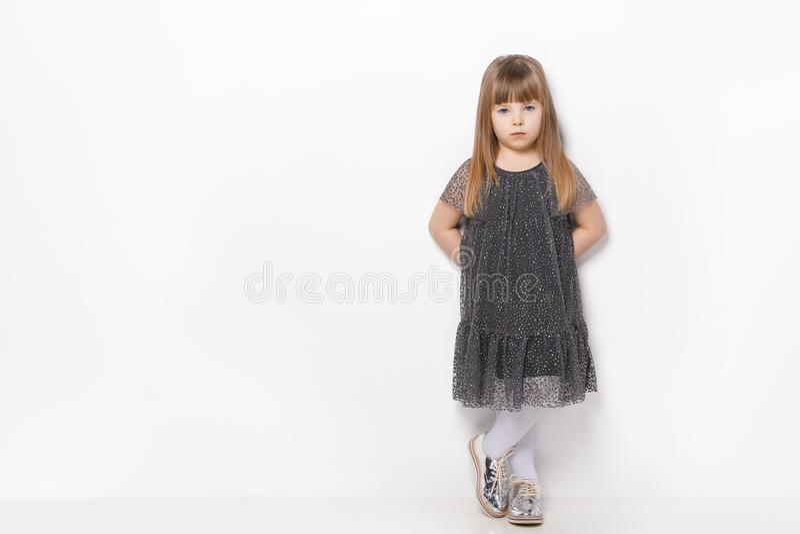 Niña hermosa con el pelo rubio y los ojos azules que se colocan en el vestido que lleva del fondo blanco imagen de archivo