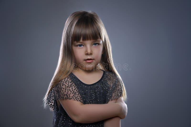 Niña hermosa con el pelo rubio y los ojos azules que se colocan en el vestido que lleva del fondo blanco foto de archivo