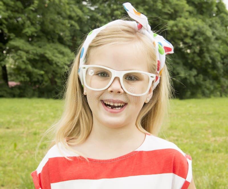 Niña hermosa con la sonrisa de los vidrios fotografía de archivo libre de regalías