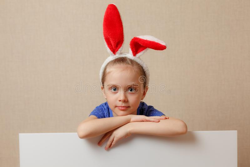 Niña hermosa con los oídos del conejito y la bandera en blanco Pascua feliz fotografía de archivo