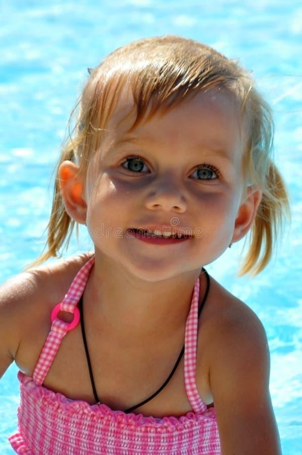 Niña hermosa con los ojos azules contra la perspectiva de la piscina imágenes de archivo libres de regalías