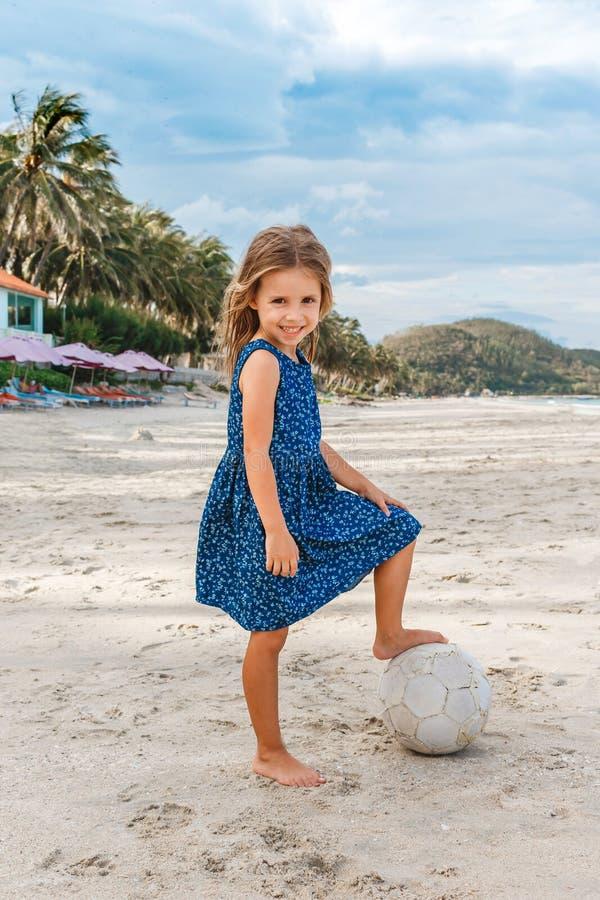 Niña hermosa con una bola en la playa fotos de archivo libres de regalías