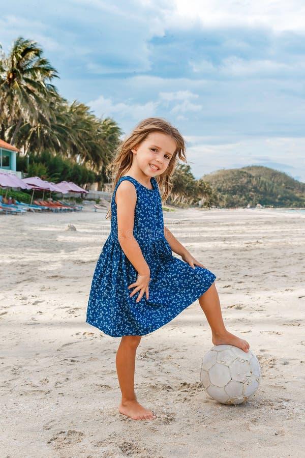 Niña hermosa con una bola en la playa imagenes de archivo