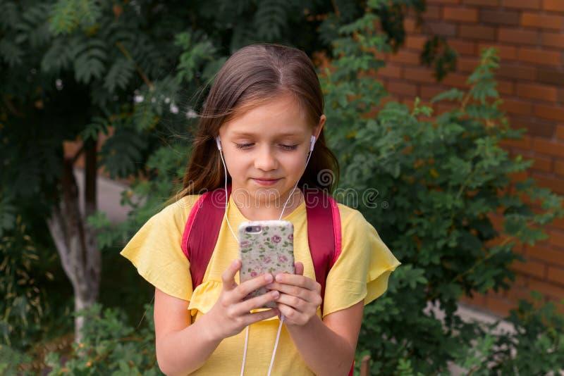 niña hermosa con una mochila usando un teléfono móvil foto de archivo