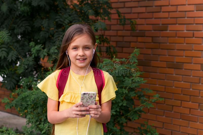 niña hermosa con una mochila usando un teléfono móvil imágenes de archivo libres de regalías
