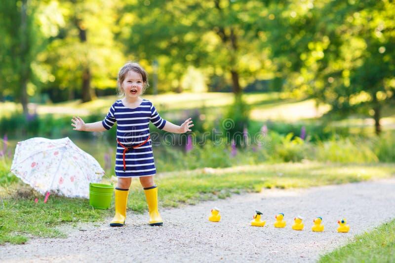 Niña hermosa de 2 que juegan con los patos de goma amarillos en s imágenes de archivo libres de regalías