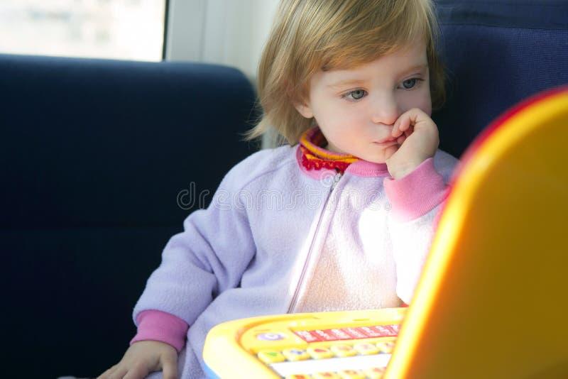 Niña hermosa del niño con el ordenador del juguete imagen de archivo libre de regalías