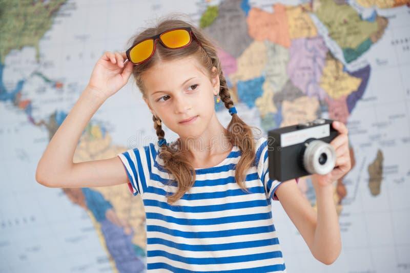 Niña hermosa en camisa y gafas de sol rayadas del marinero con el camere del vintage a disposición en fondo del mapa del mundo fotografía de archivo