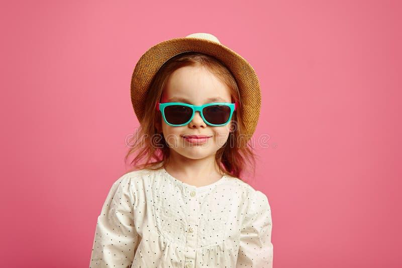 Niña hermosa en el sombrero de paja y las gafas de sol, retrato del primer en rosado aislado imagen de archivo libre de regalías