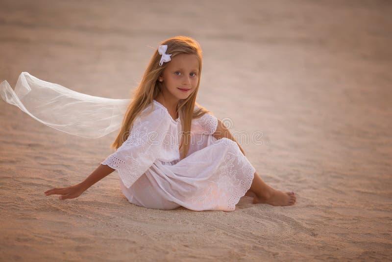 Niña hermosa en el vestido blanco que se sienta en la arena en el desierto en la puesta del sol fotos de archivo libres de regalías