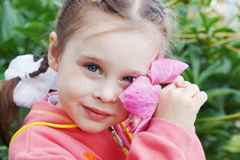 Niña hermosa en un jardín con la flor de la peonía imágenes de archivo libres de regalías