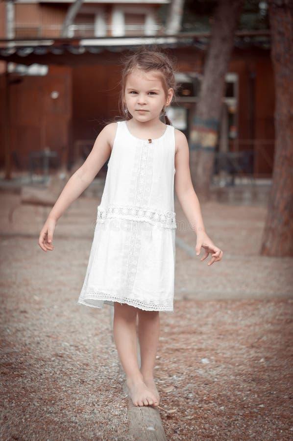 Niña hermosa en un vestido blanco que camina descalzo en un registro fotos de archivo libres de regalías
