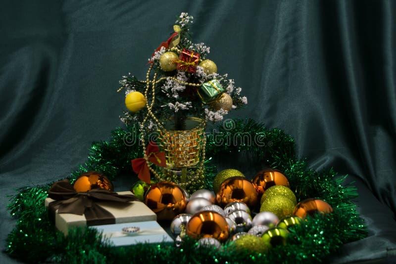 Niña hermosa en un vestido de la princesa alrededor del árbol de navidad Ella se sienta al lado del árbol de navidad con un regal fotografía de archivo