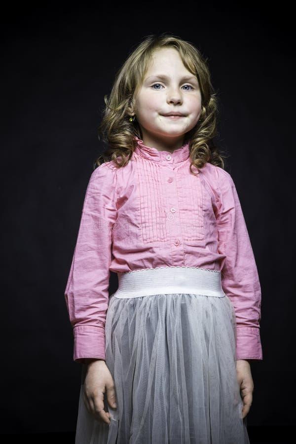 Niña hermosa en una blusa y una falda rosadas del blanco fotografía de archivo libre de regalías