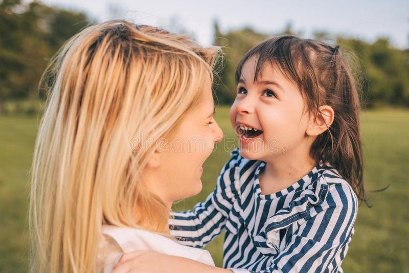 Niña hermosa feliz que ríe y que juega con su mamá bonita en el parque La madre y la hija de amor pasan el tiempo junto fotografía de archivo libre de regalías