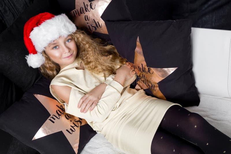Niña hermosa imponente con el pelo rubio largo que miente en una cama en un sombrero de Santa Claus imágenes de archivo libres de regalías