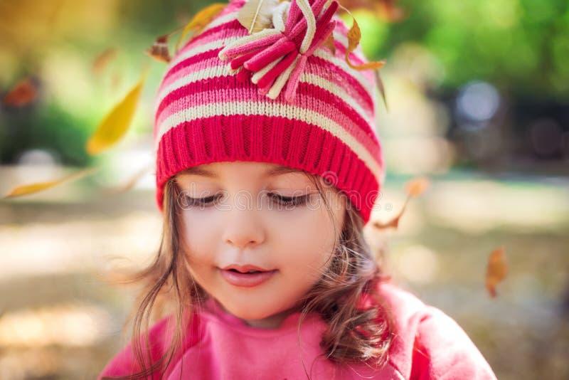 Niña hermosa que juega con las hojas caidas en el parque del otoño imágenes de archivo libres de regalías