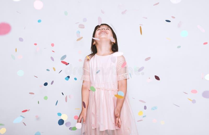 Niña hermosa que lleva el vestido rosado en Tulle con la corona de la princesa que mira para arriba a la sorpresa colorida del co foto de archivo libre de regalías