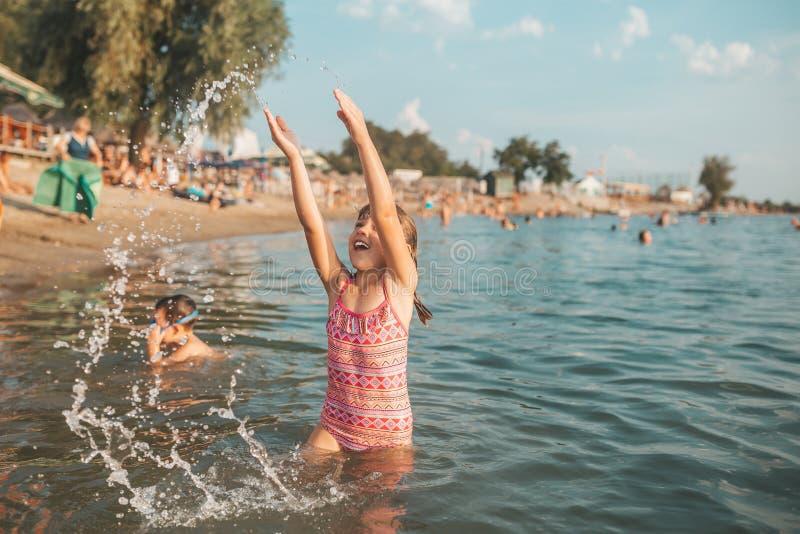 Niña hermosa que se divierte en el agua, sus manos que salpican la agua de mar fotografía de archivo libre de regalías