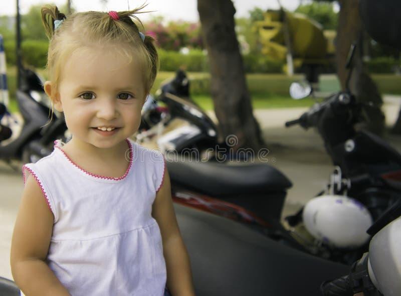 Niña hermosa que se sienta en la bici en el parque ella lo examina y estudia fotografía de archivo