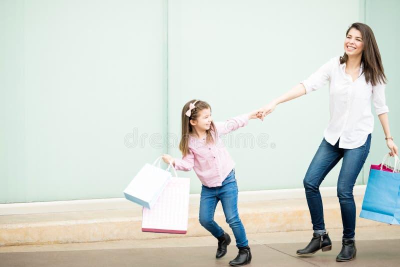 Niña hermosa que tira de la madre fuera de la alameda de compras imágenes de archivo libres de regalías