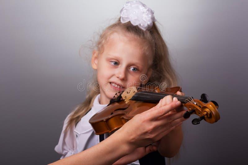 Niña hermosa que toca el violín en fondo gris foto de archivo