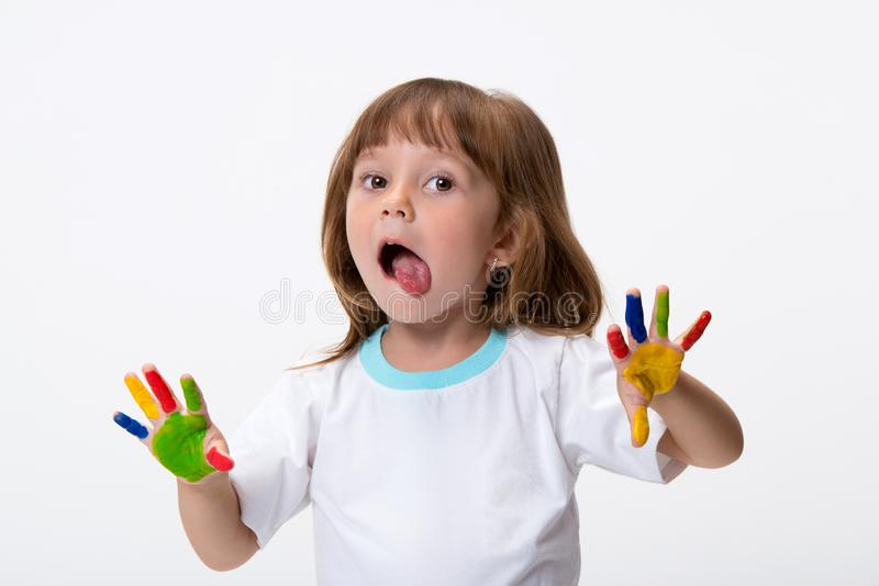 Niña hermosa sonriente feliz con sus manos coloridas en la pintura aislada en el fondo blanco imagenes de archivo