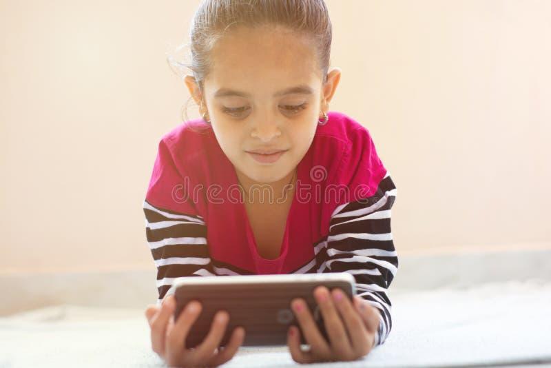 Niña india bonita con la cara sonriente usando el teléfono móvil en la cama fotos de archivo