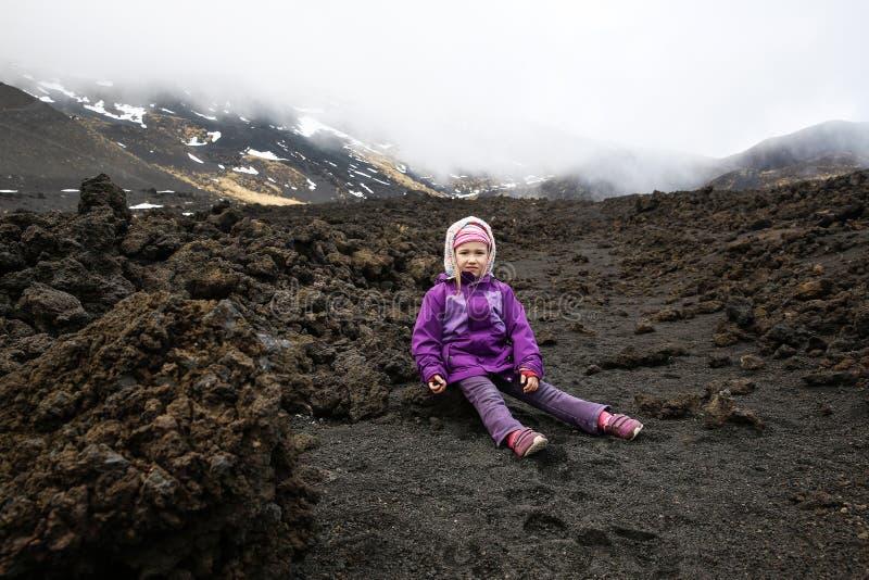 Niña irritable que descansa sobre los campos de lava del monte Etna fotos de archivo libres de regalías
