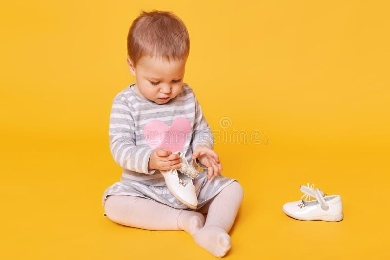 Niña joven en vestido rayado con el corazón rosado y las medias que se sientan en fondo amarillo en estudio y que juegan con su foto de archivo