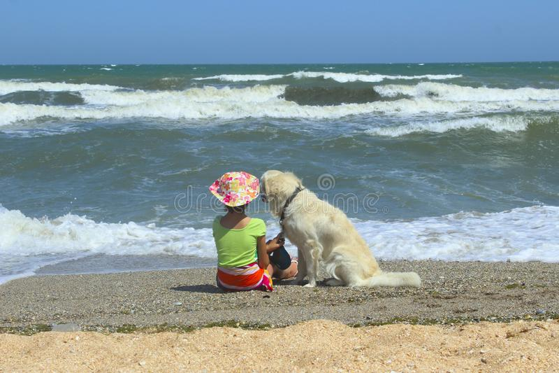 Niña joven y perro del golden retriever que se sienta en la playa Muchacha que se sienta solamente con su perro fotografía de archivo