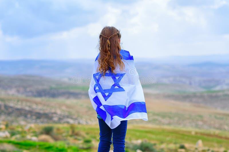 Niña judía israelí con la opinión trasera de la bandera de Israel imágenes de archivo libres de regalías