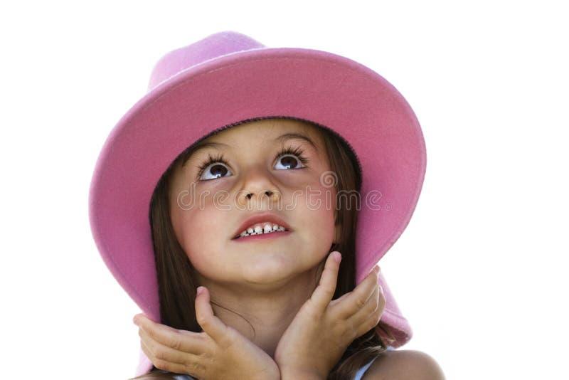 Niña juguetona con un sombrero encendido imagenes de archivo