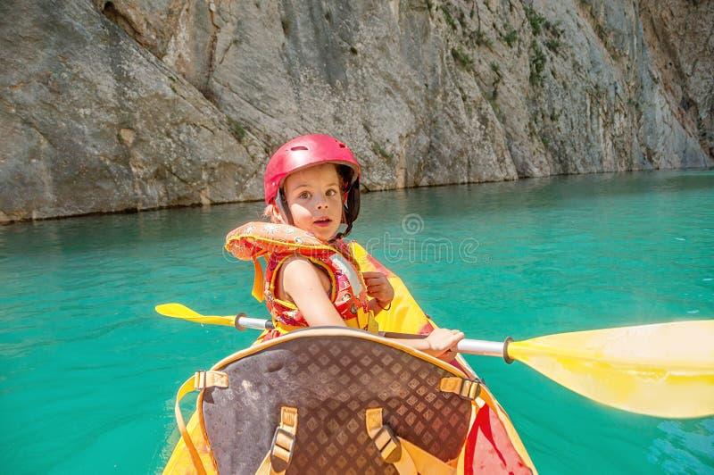 Niña kayaking en el río hermoso, divirtiéndose y disfrutando de deportes al aire libre Deporte acuático y diversión que acampa Ga imagen de archivo