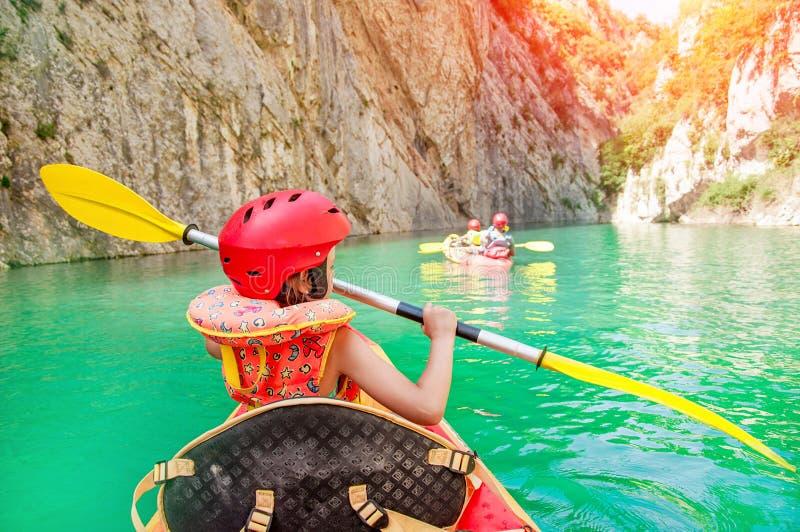 Niña kayaking en el río hermoso, divirtiéndose y disfrutando de deportes al aire libre Deporte acuático y diversión que acampa Ga fotos de archivo