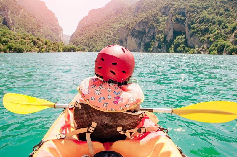 Niña kayaking en el río hermoso, divirtiéndose y disfrutando de deportes al aire libre Deporte acuático y diversión que acampa Ga imágenes de archivo libres de regalías
