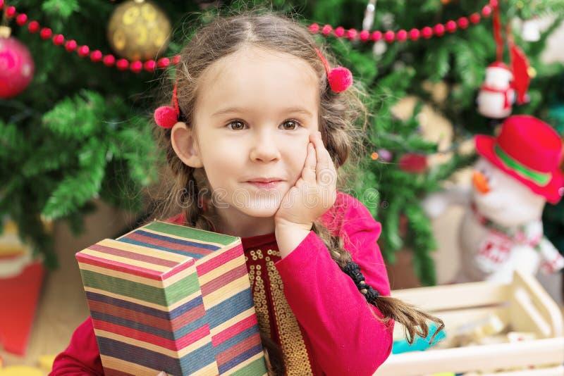Niña linda cerca del árbol de navidad hermoso con un regalo imagenes de archivo