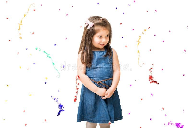 Niña linda con el confeti que cae alrededor imagenes de archivo