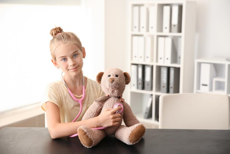 Niña linda con el oso del estetoscopio y de peluche en casa foto de archivo libre de regalías