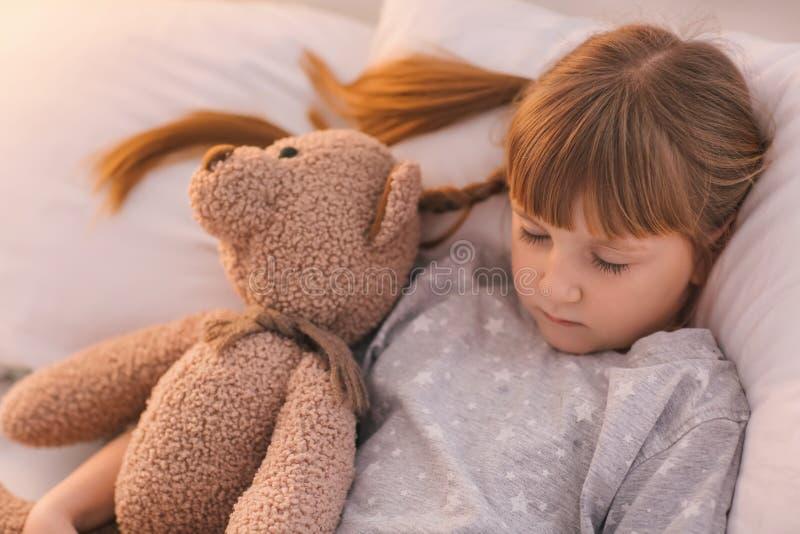 Niña linda con el oso del juguete que duerme en cama fotografía de archivo