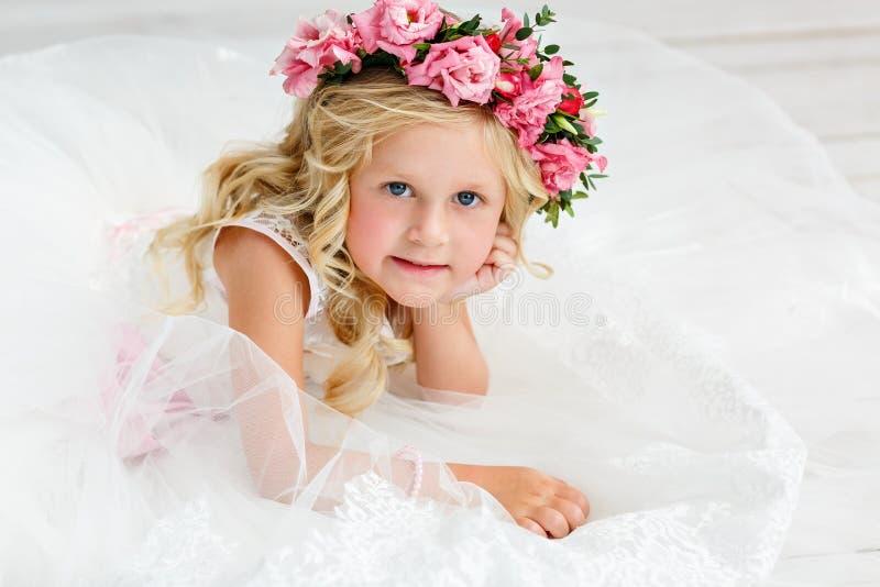 Niña linda con el pelo rubio en un estudio brillante con una guirnalda de flores rosadas Mirada de la c?mara y sonrisa fotografía de archivo libre de regalías