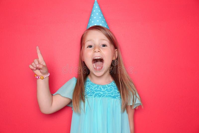 Niña linda con el sombrero del cumpleaños y el dedo índice aumentado en fondo del color imagen de archivo libre de regalías
