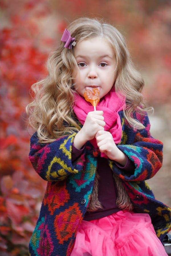 Niña linda con la piruleta en el fondo de la naturaleza hermosa del parque del otoño fotografía de archivo