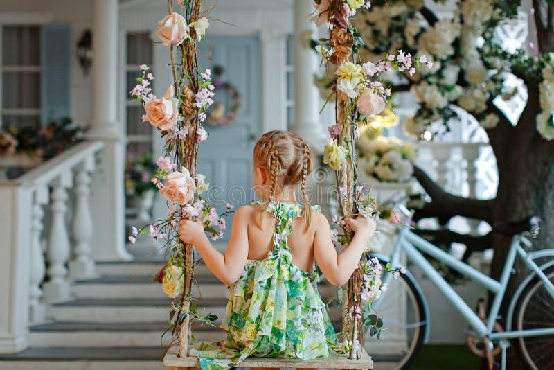 Niña linda con las coletas en un vestido verde que se sienta en el oscilación fotos de archivo