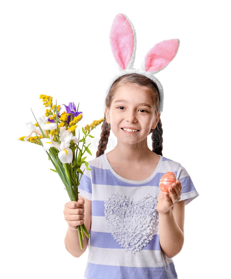 Niña linda con los oídos del conejito que sostienen las flores y el huevo de Pascua hermosos en el fondo blanco imagen de archivo libre de regalías