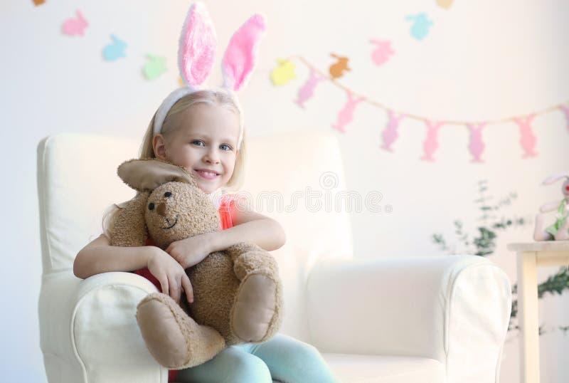 Niña linda con los oídos del conejito y el juguete mimoso que se sientan en butaca imagen de archivo libre de regalías