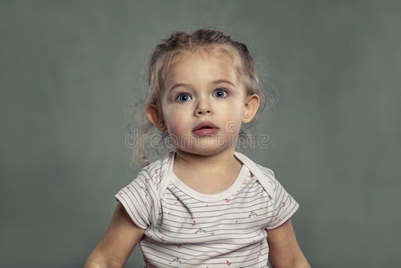 Niña linda con los ojos azules grandes Fondo gris foto de archivo libre de regalías